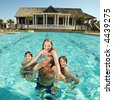 Caucasian family at pool with clubhouse in background. - stock