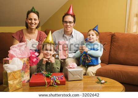 Caucasian family celebrating a birthday party and looking at viewer. - stock photo