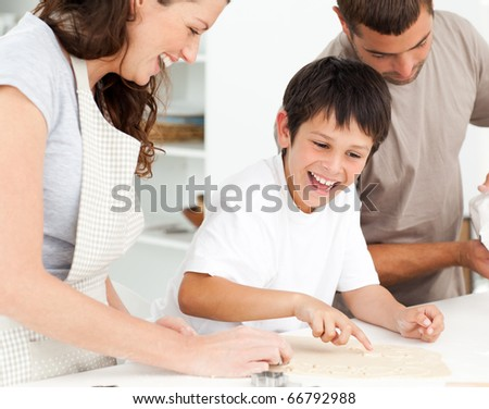 Caucasian family cooking biscuits together in the kitchen - stock photo