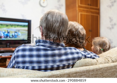 Caucasian family from three people sitting on the couch and watching tv, rear view - stock photo