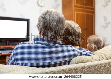 Caucasian family from three people sitting on the sofa and watching tv set, rear view, isolated white screen - stock photo
