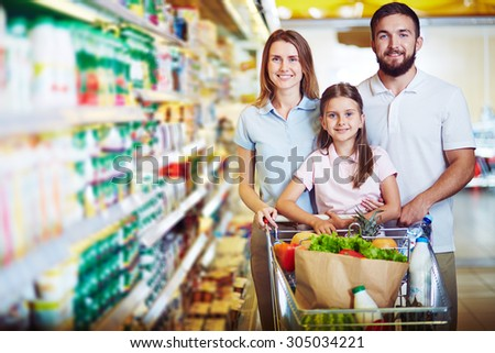 Caucasian family looking at camera in modern hypermarket - stock photo