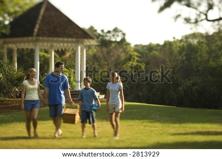 Caucasian family of four carrying picnic basket walking through park. - stock photo
