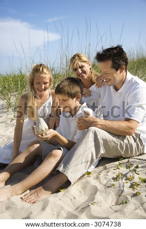 Caucasian family of four sitting on beach looking at seashell. - stock photo