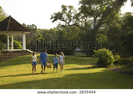 Caucasian family of four walking in park carrying picnic basket. - stock photo
