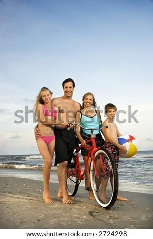 Caucasian family of four walking on beach. - stock photo