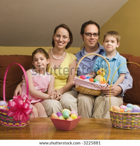 Caucasian family on couch holding Easter basket and looking at viewer. - stock photo