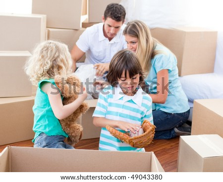 Caucasian family packing boxes while moving house - stock photo