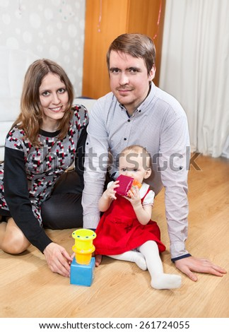Caucasian family playing together on floor of domestic room - stock photo