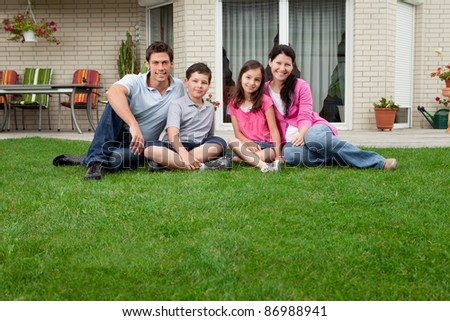 Caucasian family portrait sitting in front of their house smiling - stock photo