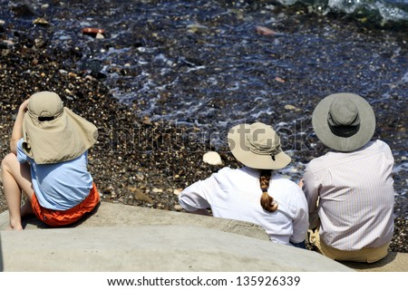 Caucasian family protect themselves from the strong sun, in Mutrah, Muscat, Oman, Middle East - stock photo