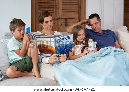Caucasian family relaxing at home mom reading magazine kids playing games on tablet device and mobile cell phone - stock photo
