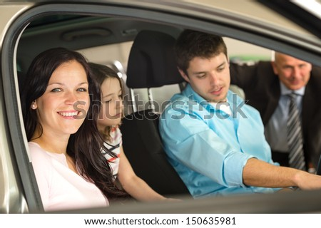 Caucasian family sitting in car in retail store - stock photo