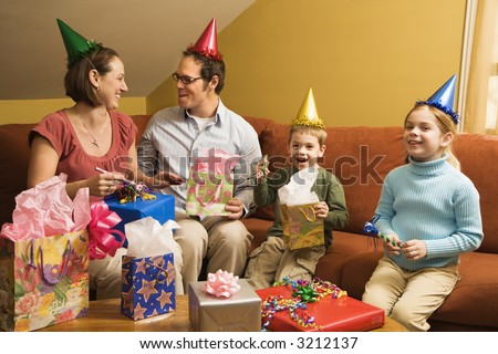 Caucasian family wearing party hats and celebrating a birthday party. - stock photo