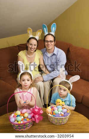 Caucasian family wearing rabbit ears with Easter baskets looking at viewer. - stock photo
