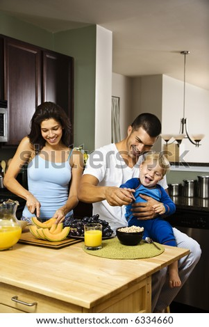 Caucasian family with toddler in kitchen at breakfast. - stock photo