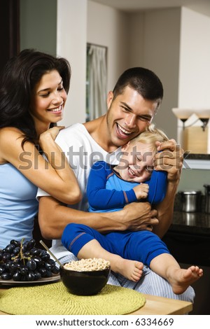 Caucasian family with toddler son in kitchen at breakfast smiling and tickling.