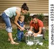 Caucasian family with toddler son washing English Bulldog in backyard. - stock
