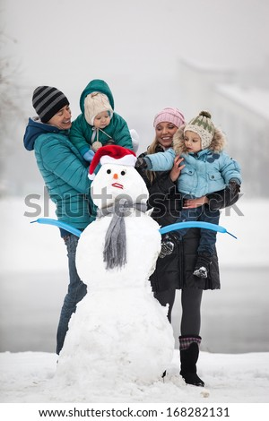 Caucasian family with two sons beside snowman outdoors - stock photo