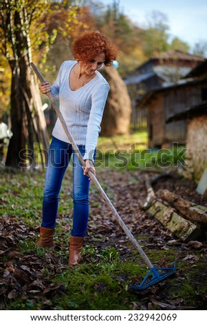 Caucasian farmer woman with a rake cleaning her garden of fallen leaves