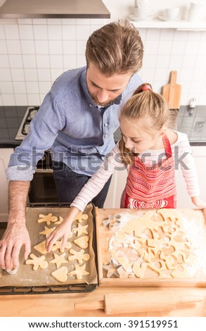 Caucasian father and daughter preparing cookies to bake. Kitchen - happy family time. - stock photo