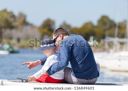 caucasian father and his son sitting at a marina dock together - stock photo