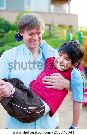 Caucasian father carrying biracial disabled son on playground - stock photo