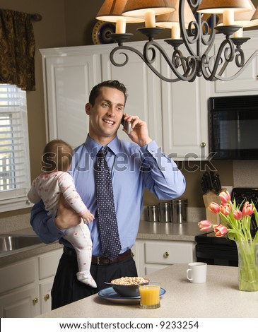 Caucasian father in suit holding baby  and talking on cellphone in kitchen. - stock photo