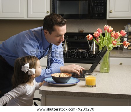 Caucasian father in suit using laptop computer with daughter eating breakfast in kitchen. - stock photo