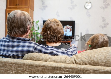 Caucasian father, mother and daughter sitting on the couch and watching tv, rear view - stock photo