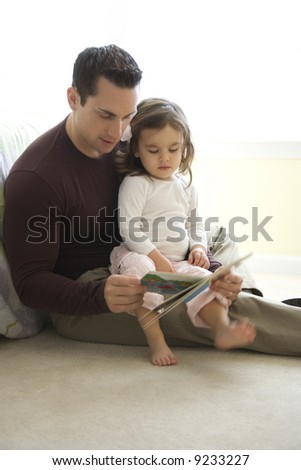 Caucasian father reading book to girl on lap sitting on floor.