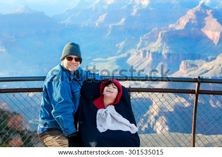 Caucasian father sitting next to biracial disabled son in wheelchair at Grand Canyon, Arizona, USA - stock photo