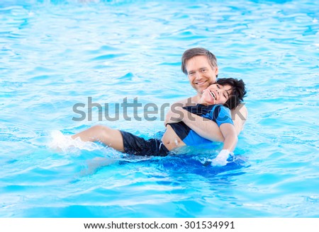 Caucasian father swimming in pool with biracial disabled son in his arms. Child has cerebral palsy. - stock photo