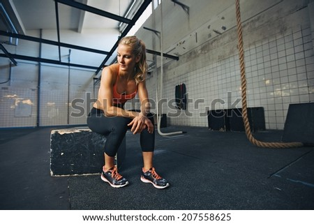 Caucasian female athlete sitting on a box at gym thinking. Fit young woman taking break after her workout at gym. - stock photo