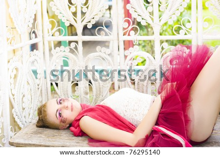 Caucasian Female Ballerina Doll In Beautiful Cosmetics Lays Down On A Wooden Bench Wearing A Cherry Colored Tutu In A Fresh Portrait Titled Sleeping Beauty - stock photo
