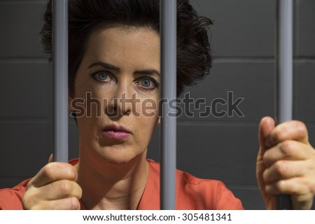 Caucasian female behind bars in a jail cell - stock photo