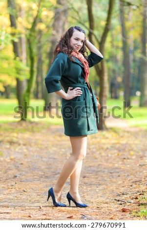 Caucasian Female Brunette Model Posing in Autumn Forest and smiling. Vertical Image Composition - stock photo