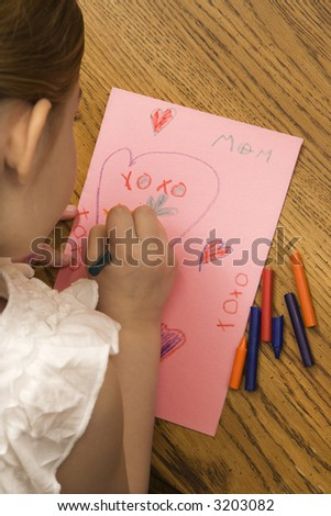 Caucasian female child drawing on paper with crayons. - stock photo