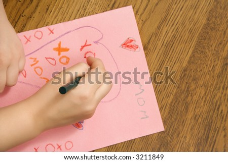 Caucasian female child hands drawing on paper with crayons. - stock photo