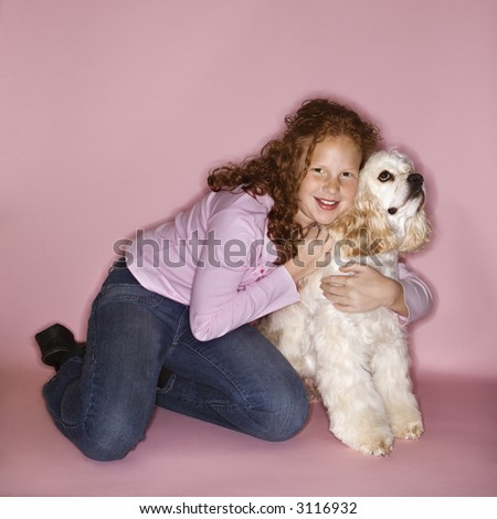 Caucasian female child hugging Cocker Spaniel dog. - stock photo