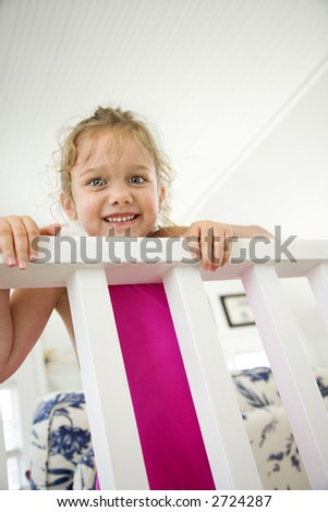 Caucasian female child peeking over railing.