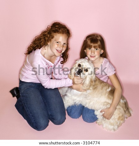 Caucasian female children holding Cocker Spaniel dog. - stock photo