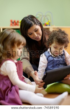 Caucasian female educator and little girls reading fairy tale on touch pad computer in kindergarten - stock photo