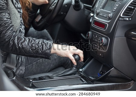 Caucasian female hand holding levels of automatic car gearbox, driver seat close-up view - stock photo