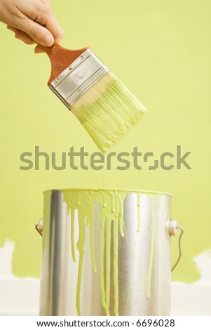 Caucasian female hand holding paintbrush over paint can.