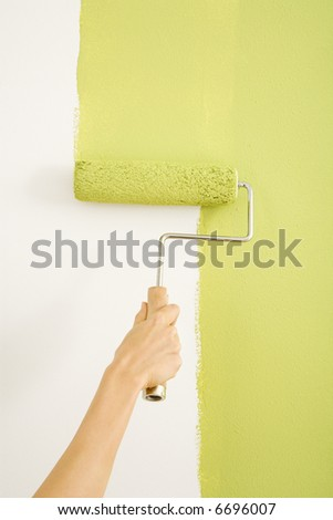 Caucasian female hand painting on wall with roller.