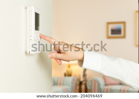 Caucasian female hand pressing button on a modern electronic thermostat timer on wall of a modern home with focus on the screen and fingers of the woman - stock photo