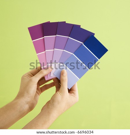 Caucasian female hands holding paint color samples.