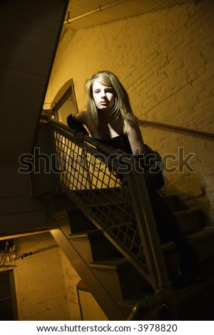 Caucasian female posing in stairwell with direct light on her face.