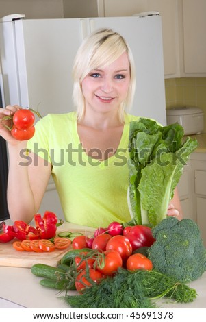 Caucasian female presenting tomatoes and lettuce holding in hands by kitchen countertop